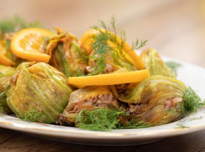 Ανθοί από κολοκύθι γεμιστοί με ρύζι, με ψιλοκομμένο άνηθο και φέτες λεμόνι, σε λευκό πιάτο