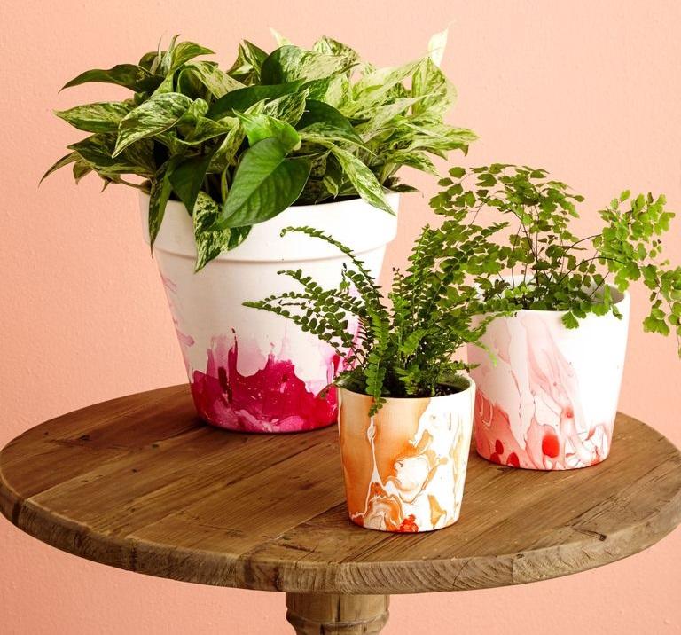 πήλινη γλάστρα από τερακότα βαμμένη με χρώματα και βερνίκια νυχιών σε λευκό, κόκκινο, ροζ και πορτοκαλί, επάνω σε τραπέζι από ξύλο, με λουλούδια και πράσινα φυτά για διακόσμηση μέσα στο σπίτι και στο μπαλκόνι