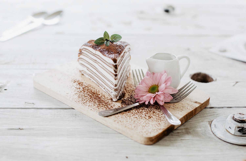 κομμάτι τούρτα με κρέπες σαντιγί και σοκολάτα επάνω σε ξύλινη βάση με πιρούνια ροζ λουλούδι χρυσάνθεμο σε ξύλινο λευκό τραπέζι