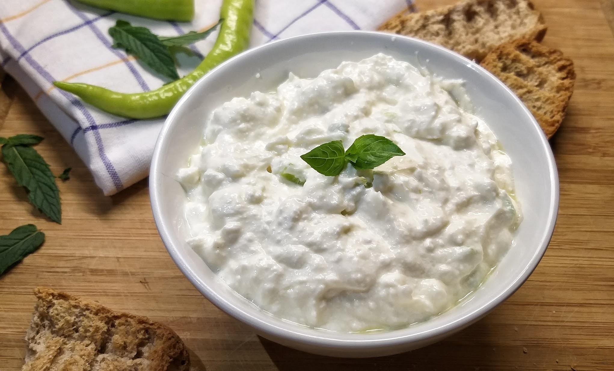 Τυροκαυτερή ή χτυπητή σαλάτα αλοιφή σε λευκό μπολ επάνω σε ξύλινο τραπέζι με φύλα δυόσμου πράσινη πιπεριά και ψωμί